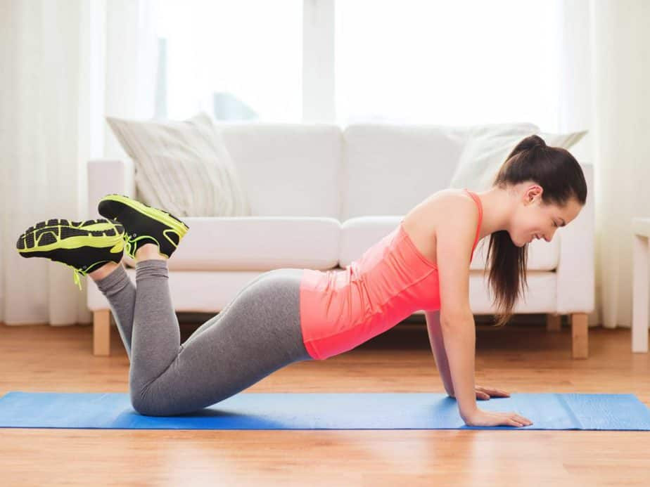 A girl has a workout on the exercise mat at home