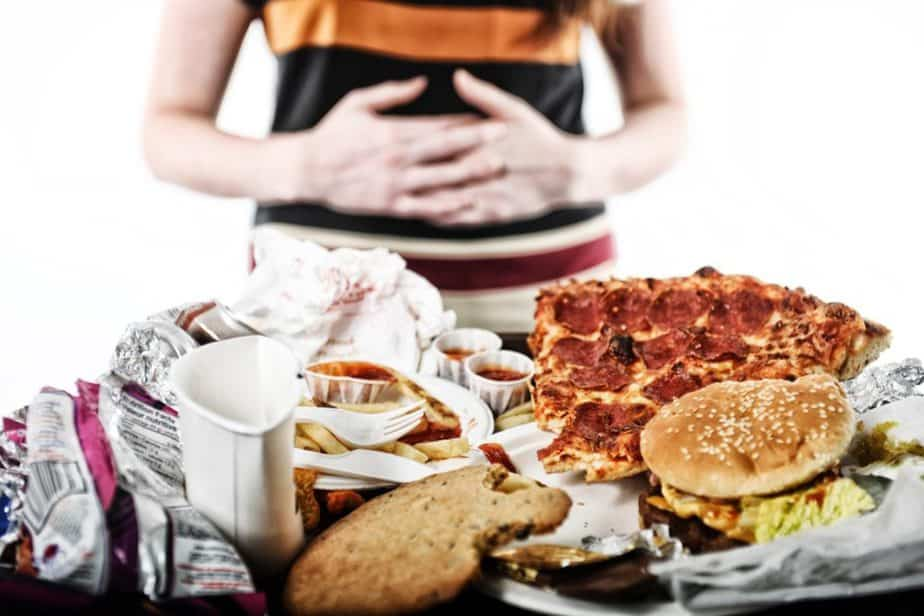 A bloated guy after overeating is having a stomachache, looking at fast food
