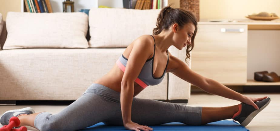 A girl is preparing for exercise with stretching at home
