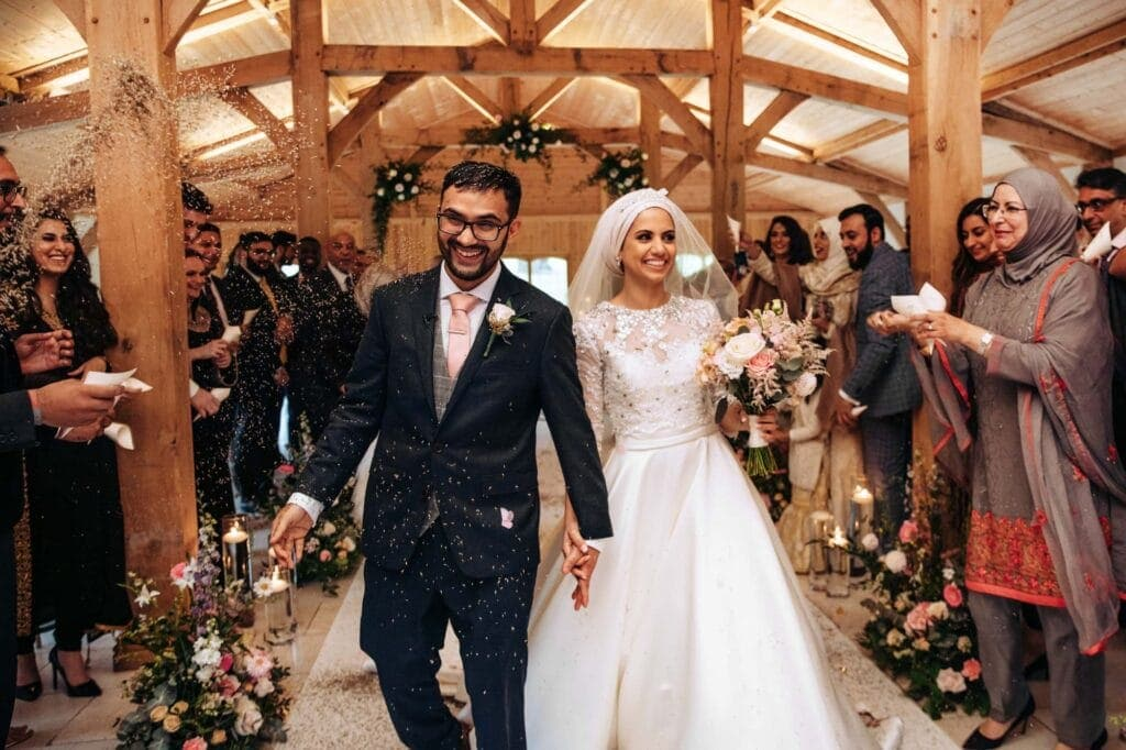 Colshaw Hall Bride and Groom walking down the aisle to confetti