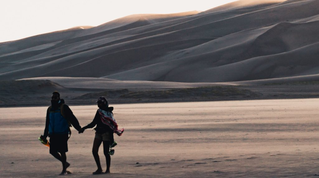 husband and wife walking in the desert