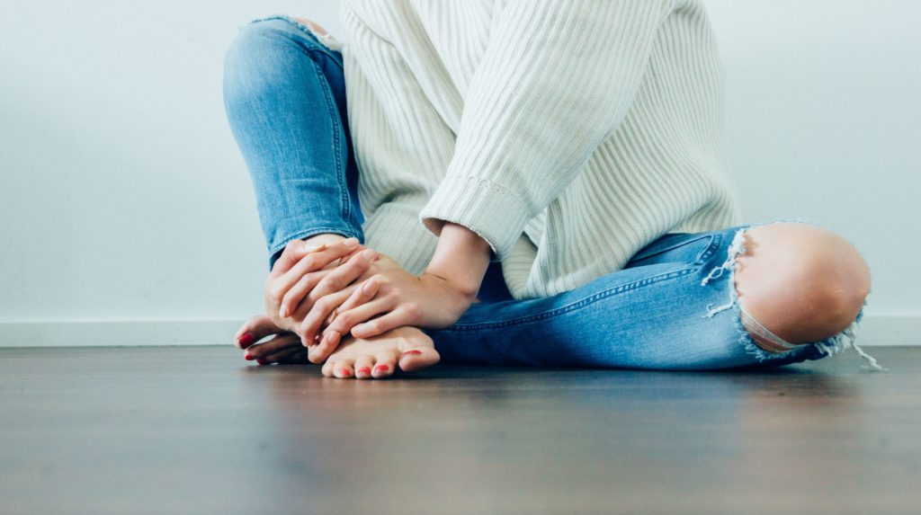 Woman wearing jeans with a hole in the knee.