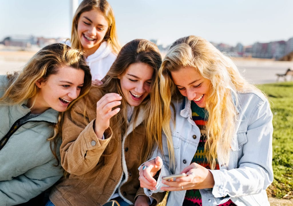 Four teenage friends having fun with her smartphone in the city