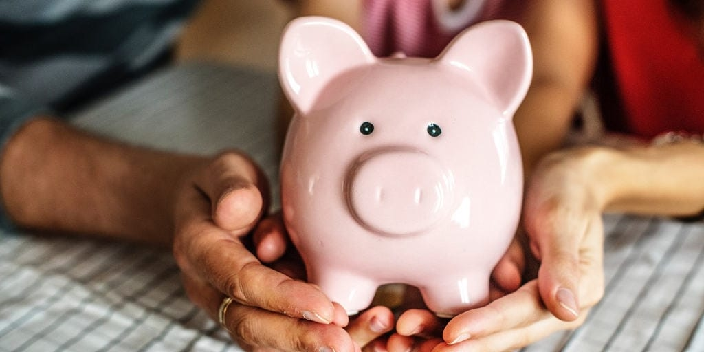 family holding a piggy bank and talking about compound interest for kids
