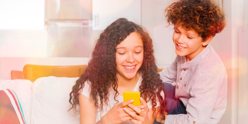 """Two kids look at allowance chore apps on their phone with text overlay """"what's the best chore app for kids?"""""""