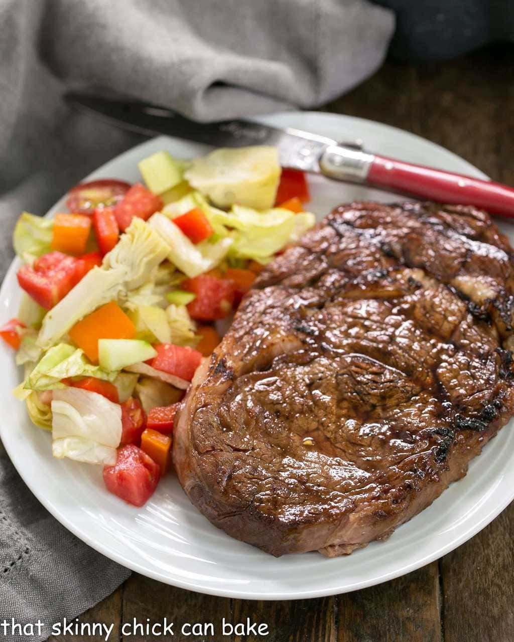 Grilled Korean Beef Steaks uncut on a white plate with a green salad
