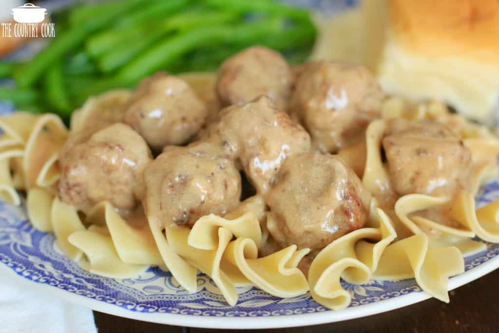 Slow Cooker Meatballs and Gravy on top of egg noodles served with green beans and a roll