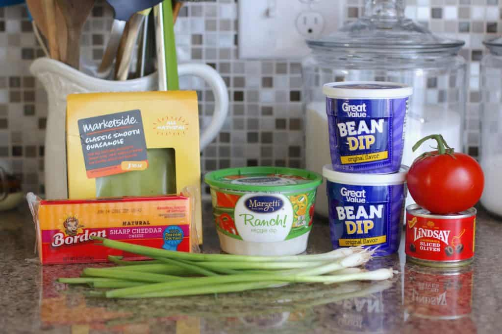 recipe ingredients been dip, ranch dip, guacamole, cheese, green onion, tomatoes, olives