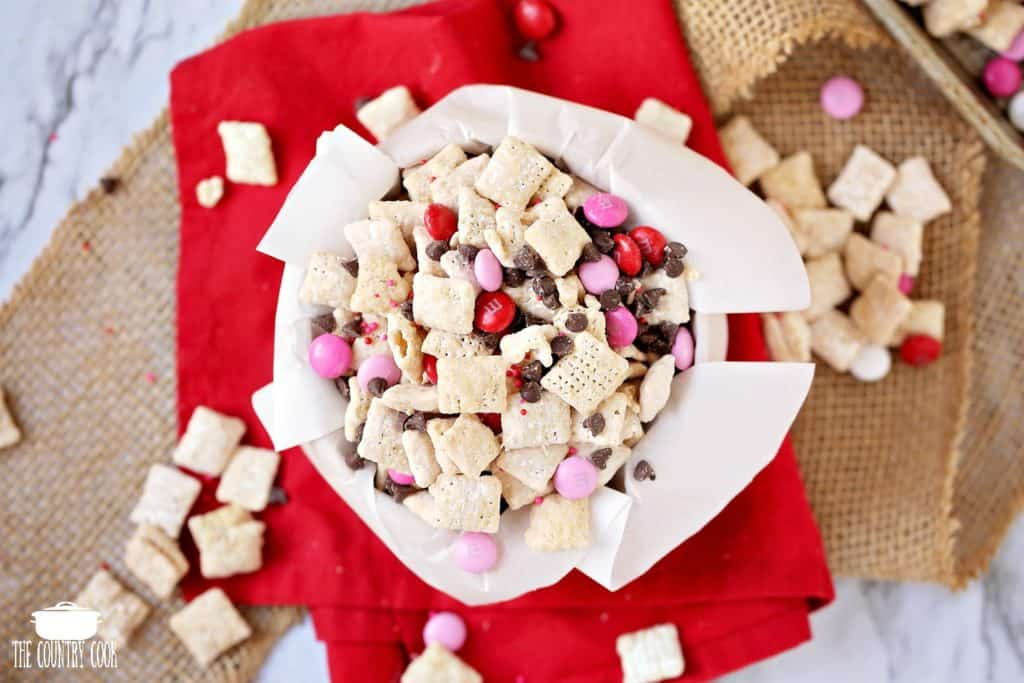 Valentine's Day Muddy Buddy Chex Mix in a bowl with parchment paper