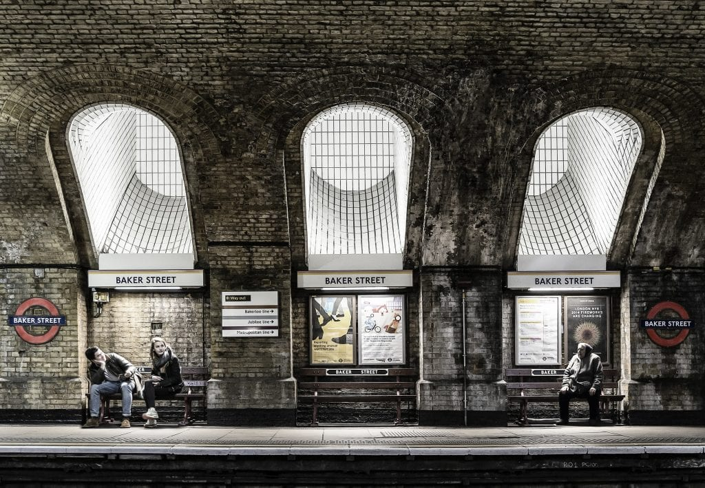 Baker Street tube station. There are two young people sat on a bench and an elderly person sat on another.