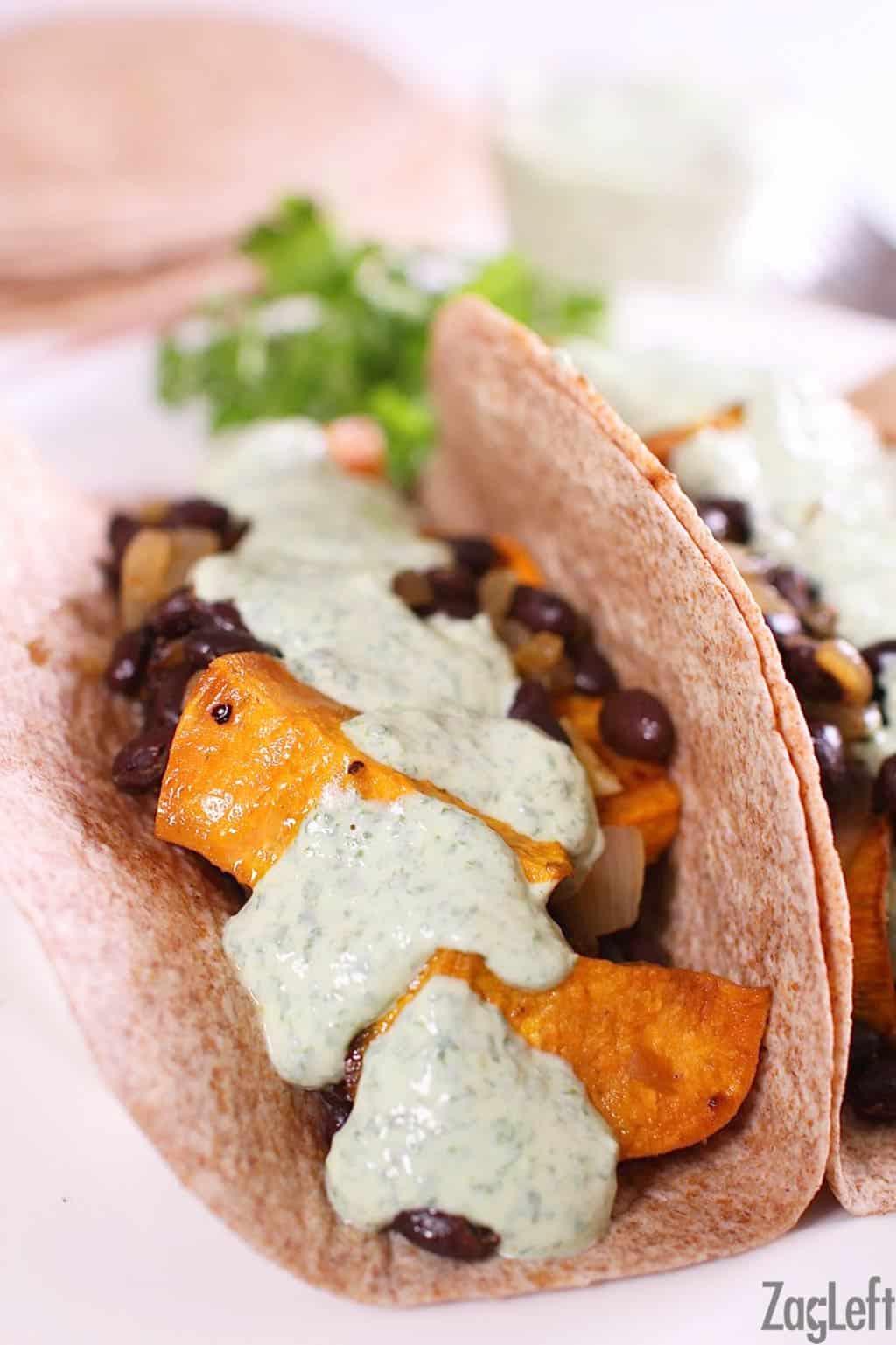 Closeup of a sweet potato black bean burrito topped with cilantro yogurt sauce in a whole wheat tortilla