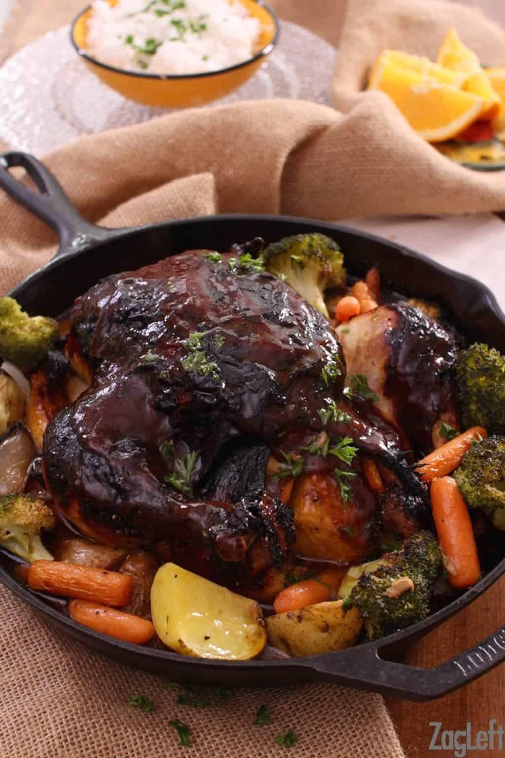 Baked chicken covered with bbq sauce with baby carrots, broccoli florets, and potatoes in a cast iron skillet with a small bowl of white rice and a small plate of orange slices in the background