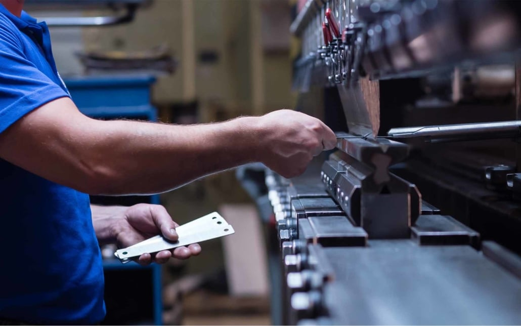 Assembly line worker using a tool to crimp metal