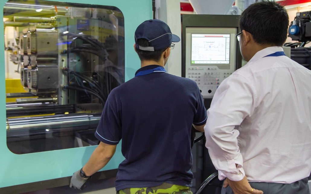 Plastic mold injection workers using an injection machine