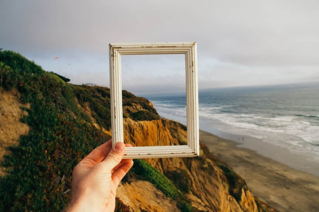 Guy holding frame on a beach