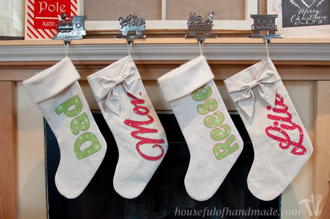 Set of 4 personalized Christmas stockings hanging on mantel.