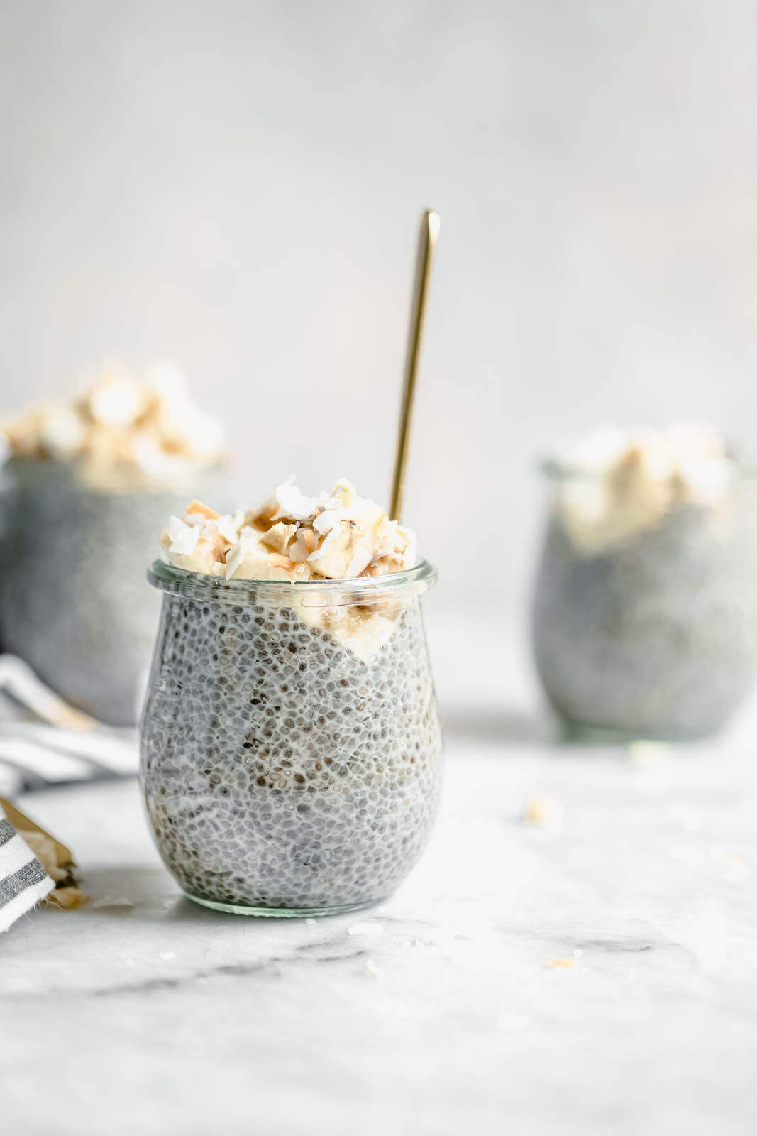 Perfect for weekday breakfast, this thick vegan Coconut Cream Pie Chia Pudding is made with almond milk and topped with banana, coconut flakes, and cashews