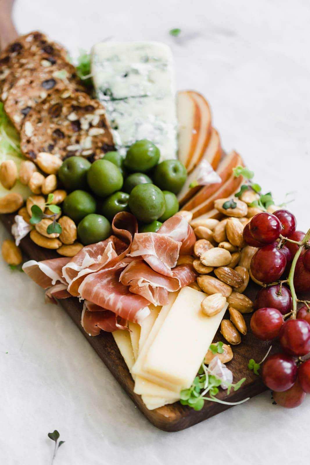 cheese board with olives, grapes, and prosciutto