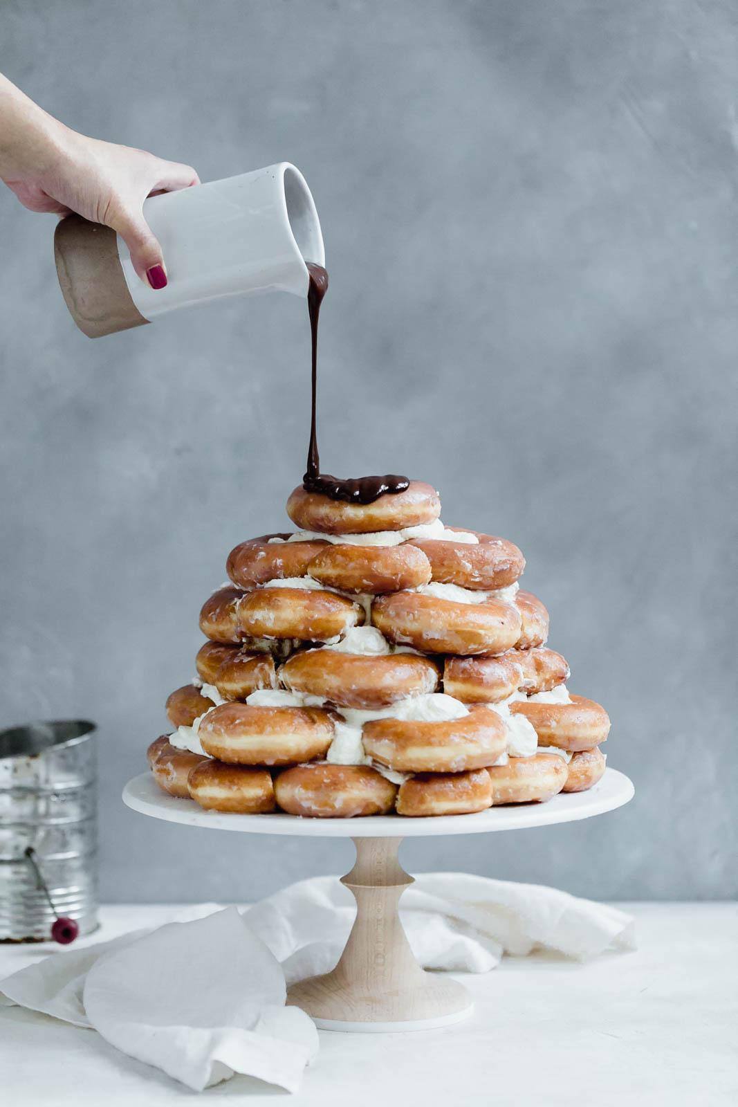 Towering Krispy Kreme donut cake smothered in chocolate frosting