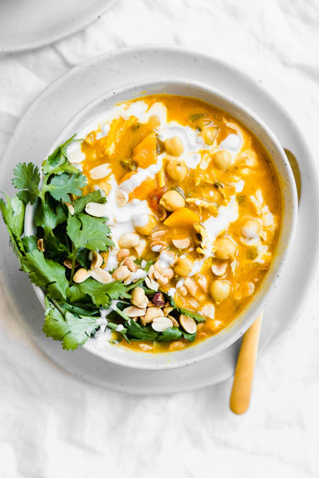 Turmeric Chicken Soup with peanuts and cilantro on top