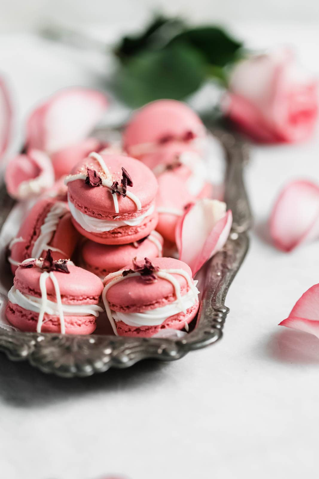 Raspberry Rose Macarons made with rosewater, a vanilla buttercream, and a surprise raspberry preserve center. Simple, elegant, and oh so delicious!!