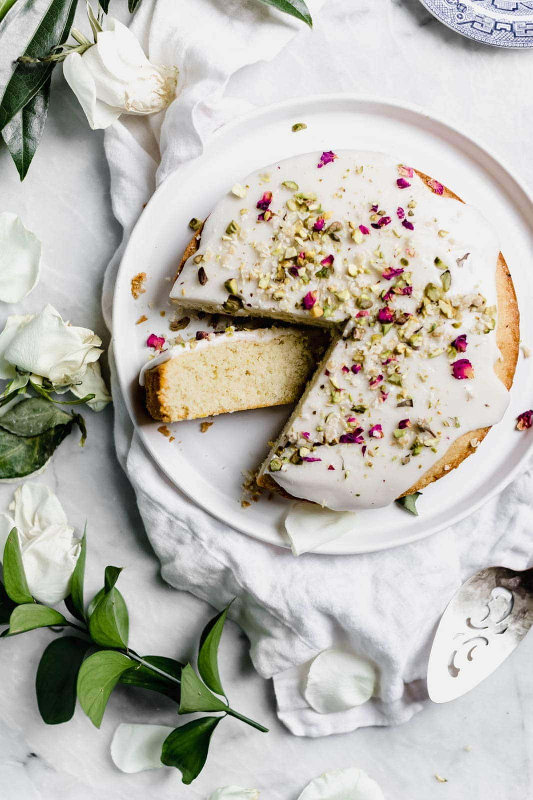 rose cake topped with glaze and pistachios