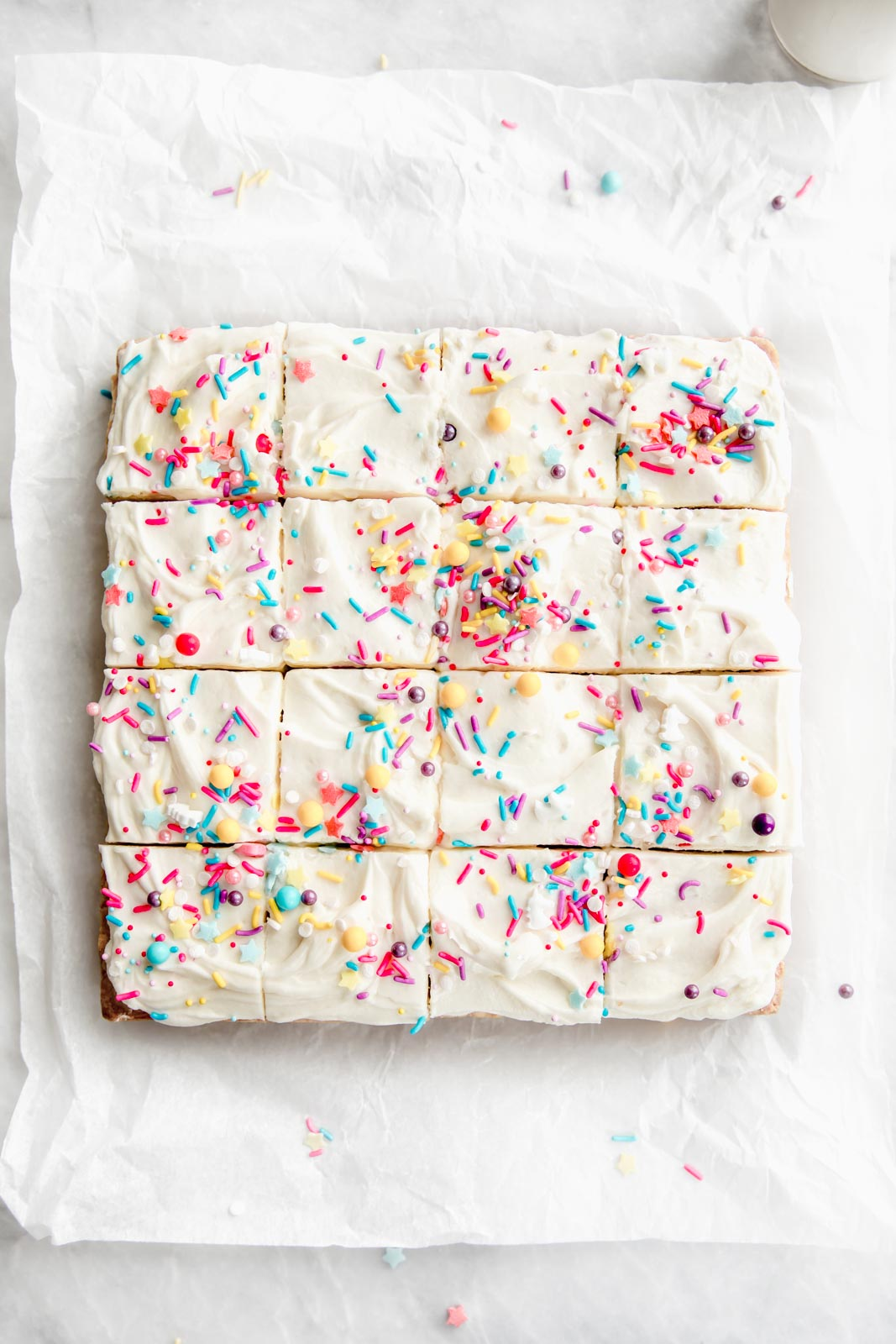 Buttery, chewy sugar cookie bars topped wtih a dreamy cream cheese frosting are the perfect easy dessert. Top this sweet treat with fun sprinkles and enjoy!