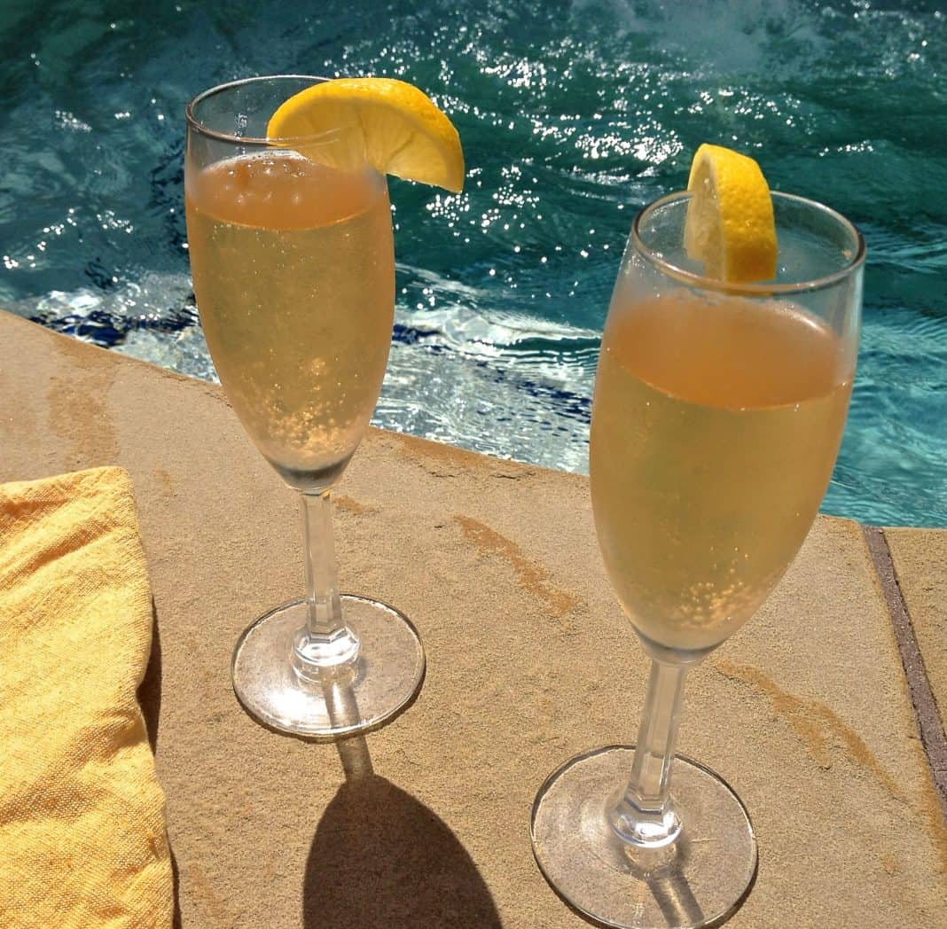 Two champagne flutes of Limoncello Champagne Aperitifs garnished with a lemon slice with a pool in the background