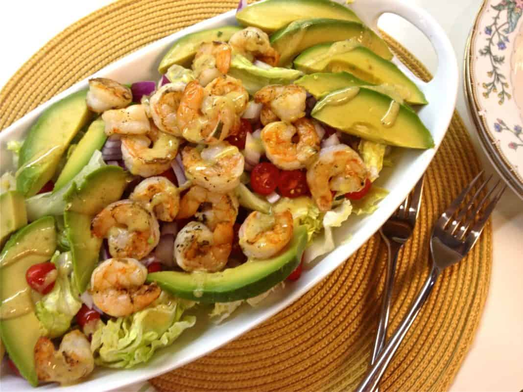 An overhead view of Grilled Shrimp and Avocado Salad with iceberg lettuce and cherry tomatoes topped with lemon mustard vinaigrette in an oval-shaped dish next to two forks and two bowls