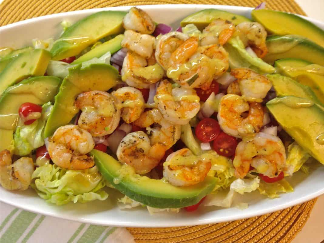 An overhead view of Grilled Shrimp and Avocado Salad with iceberg lettuce and cherry tomatoes topped with lemon mustard vinaigrette in an oval-shaped dish