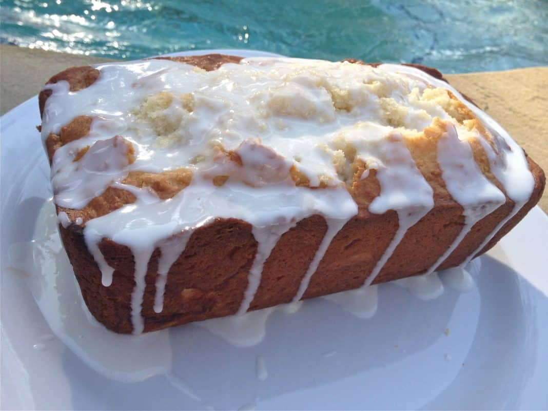 Limoncello Cake topped with Limoncello Glaze on a square plate with a pool in the background