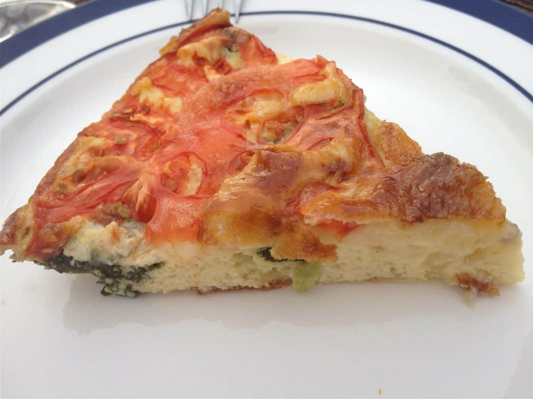 A slice of Spinach, Tomato and Brie Crustless Quiche on a plate