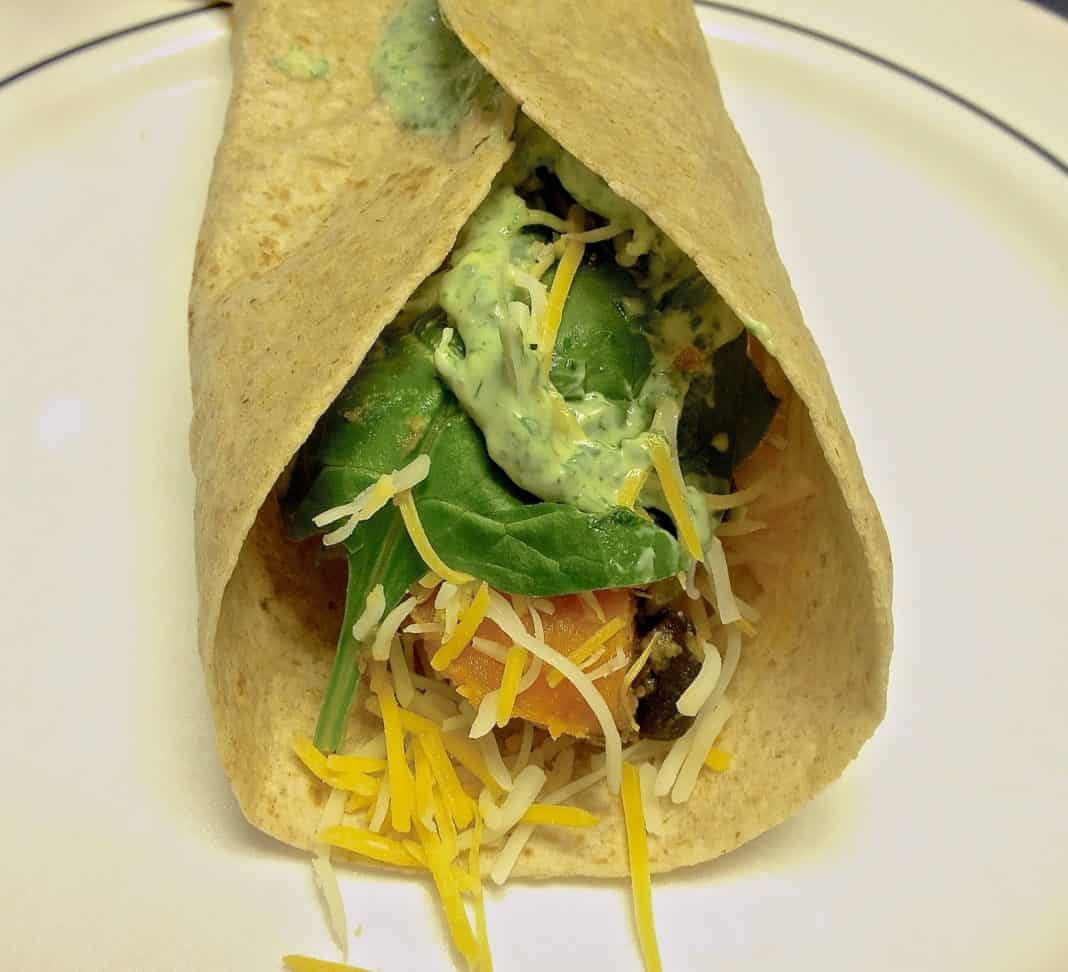 Sweet potato and black bean burrito topped with cilantro yogurt sauce and shredded cheese in a whole wheat tortilla on a plate