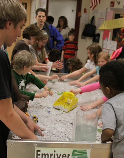 River models and young students; redesign continues.