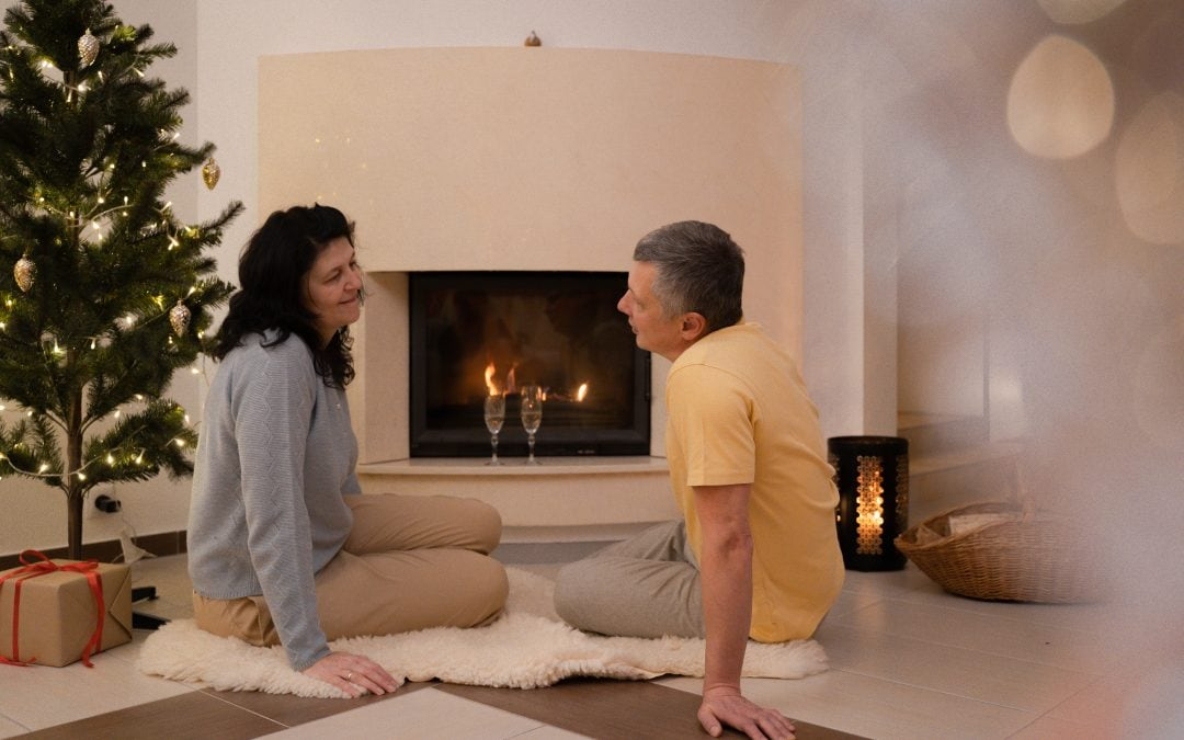 Couple sitting in front a fireplace at Christmas