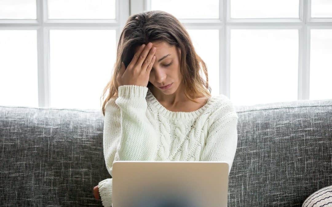Woman resting head on hand sitting on couch looking at her laptop, 14 Ways Self-Defeating Behaviors Are Sabotaging Your Business