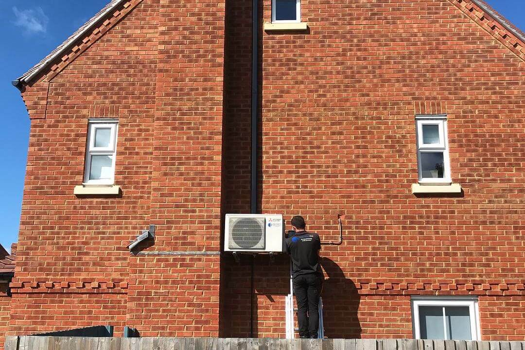 Exterior wall mounted mitsubishi electric domestic air conditioning unit neatly fitted by SubCool FM with engineer up ladder undertaking maintenance