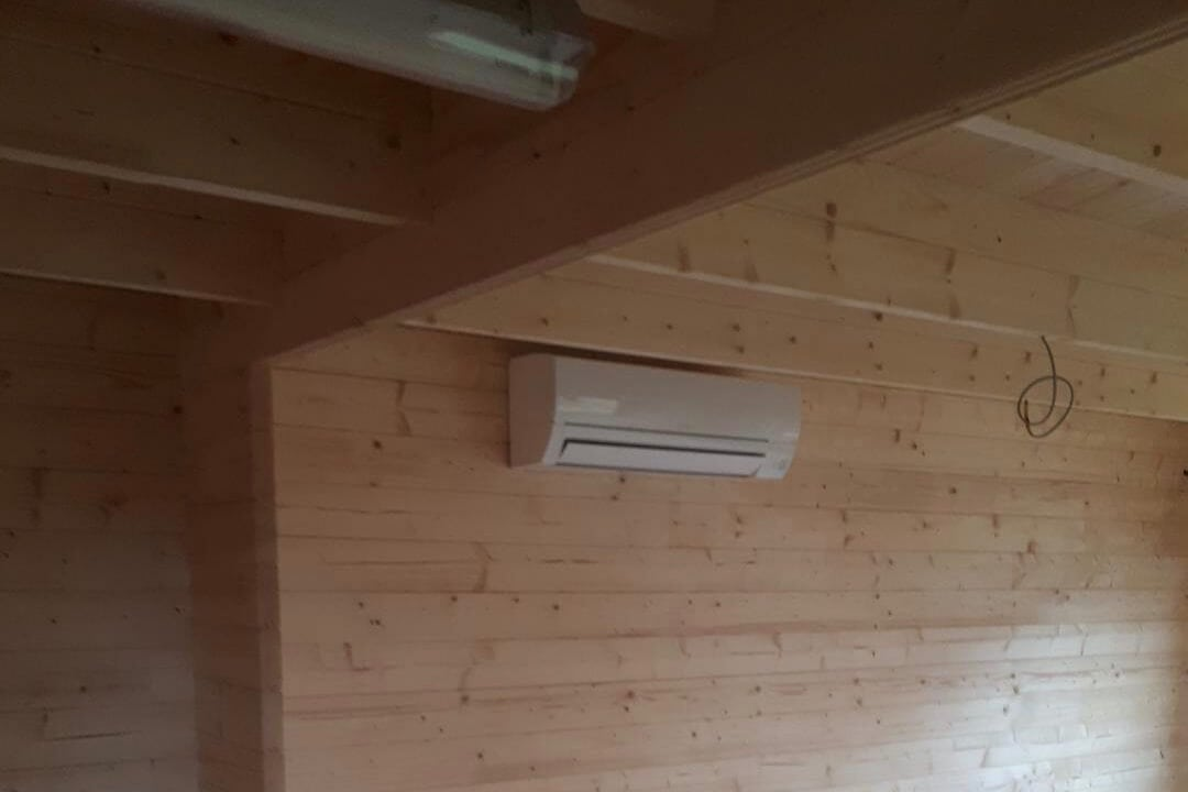 Black mitsubishi electric wall mounted unit above TV in loft conversion