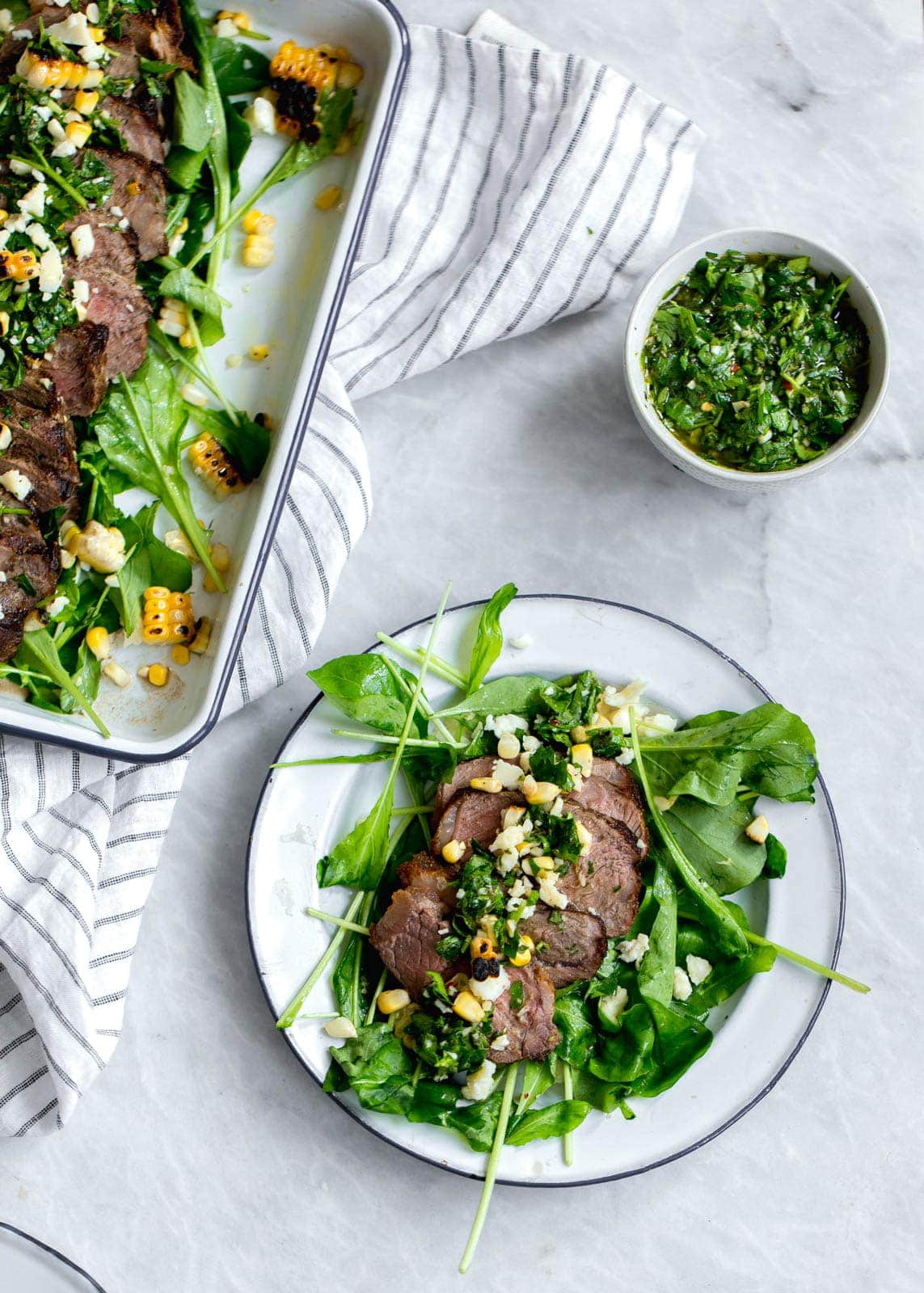 An epic Chimichurri Steak Salad with charred corn, cotija cheese, arugula, and a homemade chimichurri sauce. Perfect for summer nights!