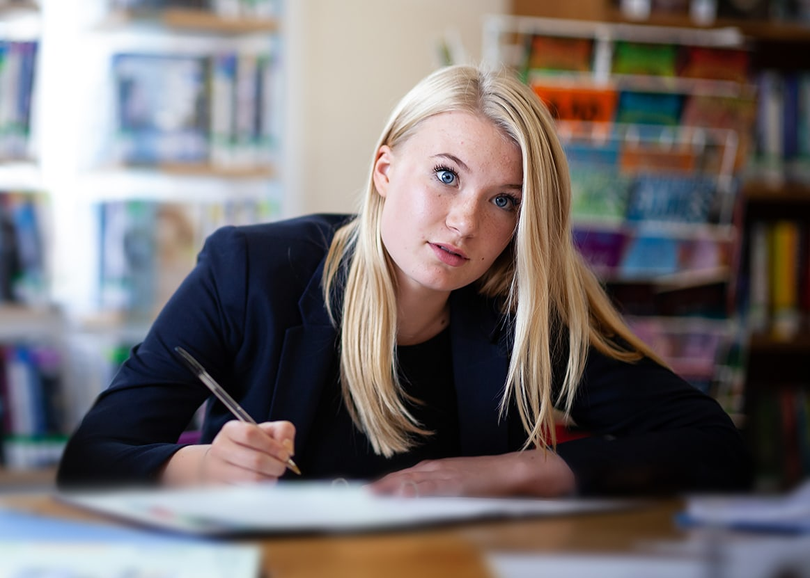 Blond girl in class studying