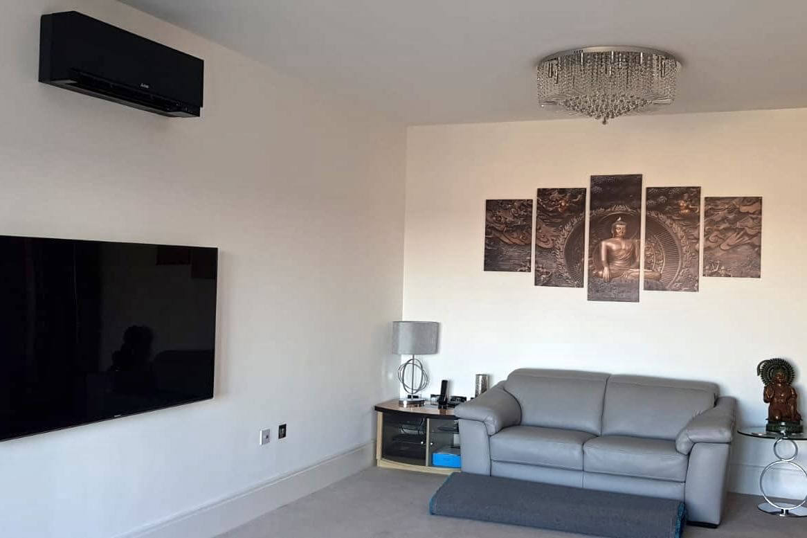 Black wall mounted mitsubishi electric domestic air conditioning unit in living space seating area over TV fitted by SubCoolFM
