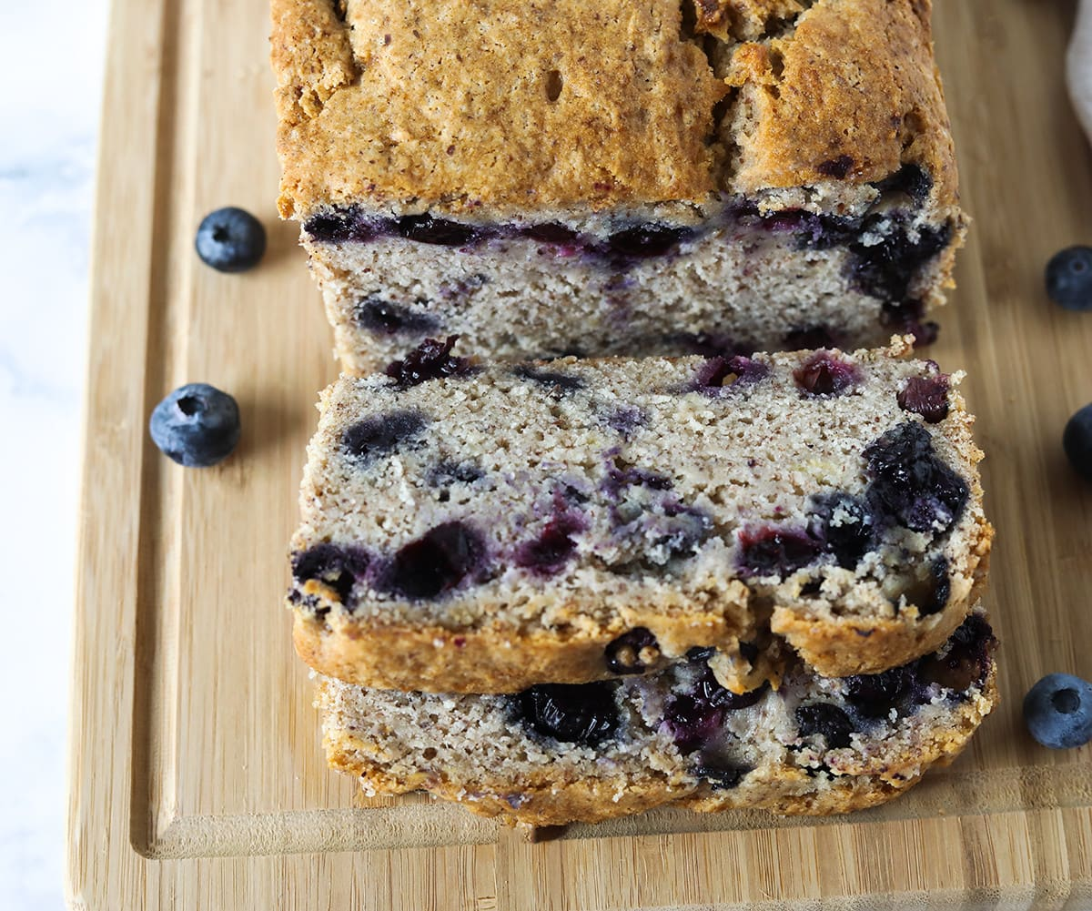 close up vegan gluten-free blueberry banana bread on a wooden board garnished with blueberries