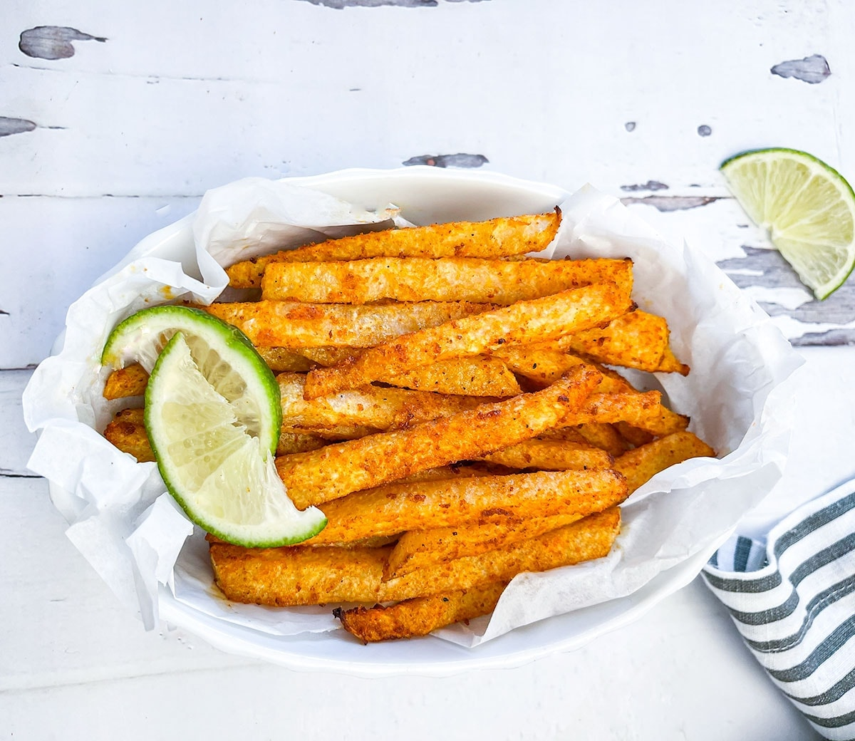 air fryer jicama fries close up in a white bowl with lime slices