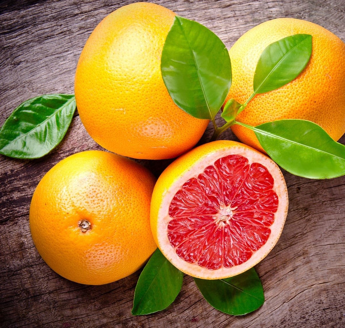 3 Whole grapefruits, one half, plus leaves on a brown wooden background