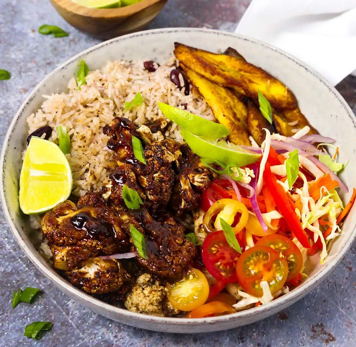 jamaican jerk cauliflower bowl in a beige bowl on a grey background