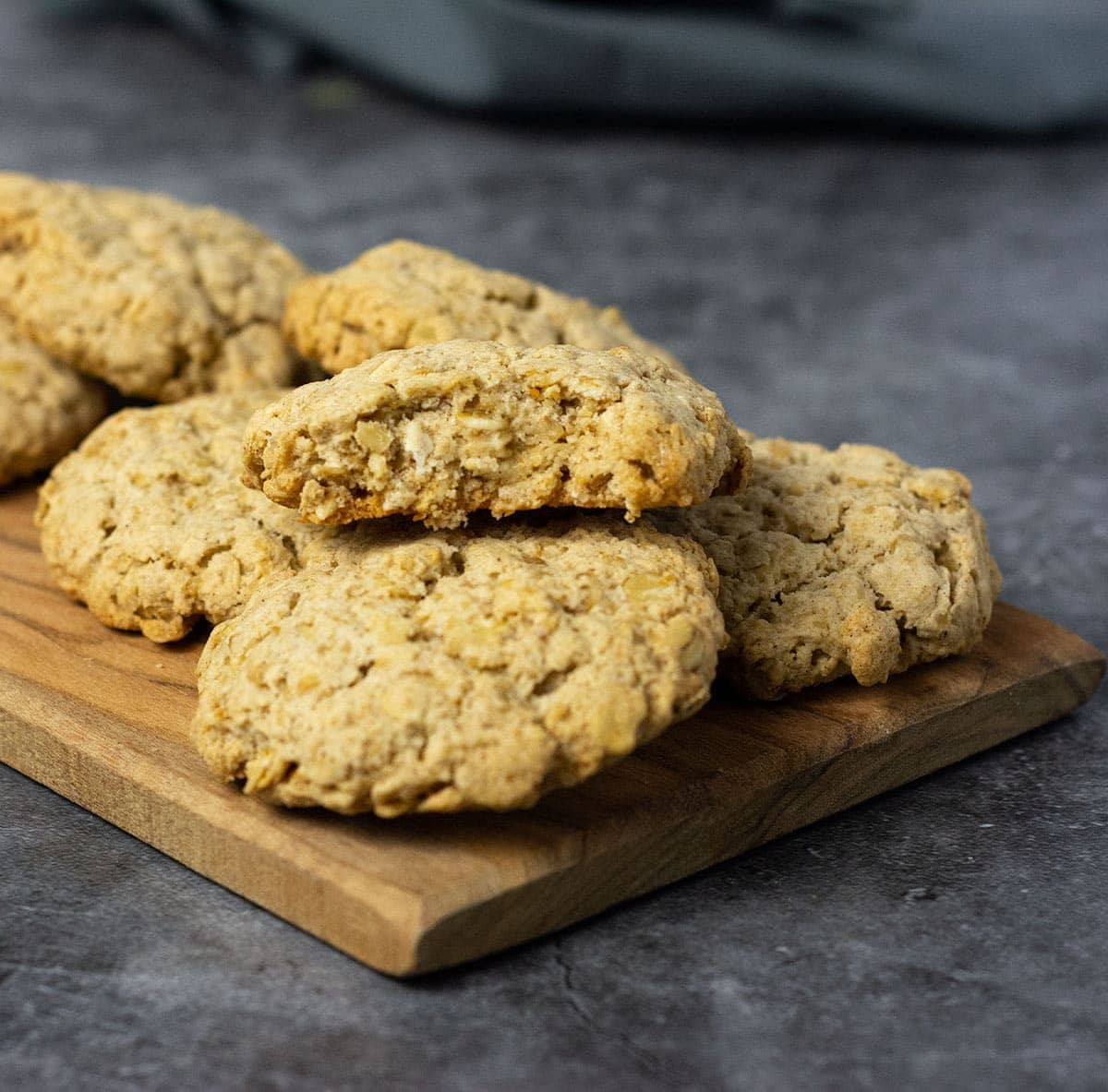 Vegan Oatmeal Cookies on a wooden cutting board on a grey background