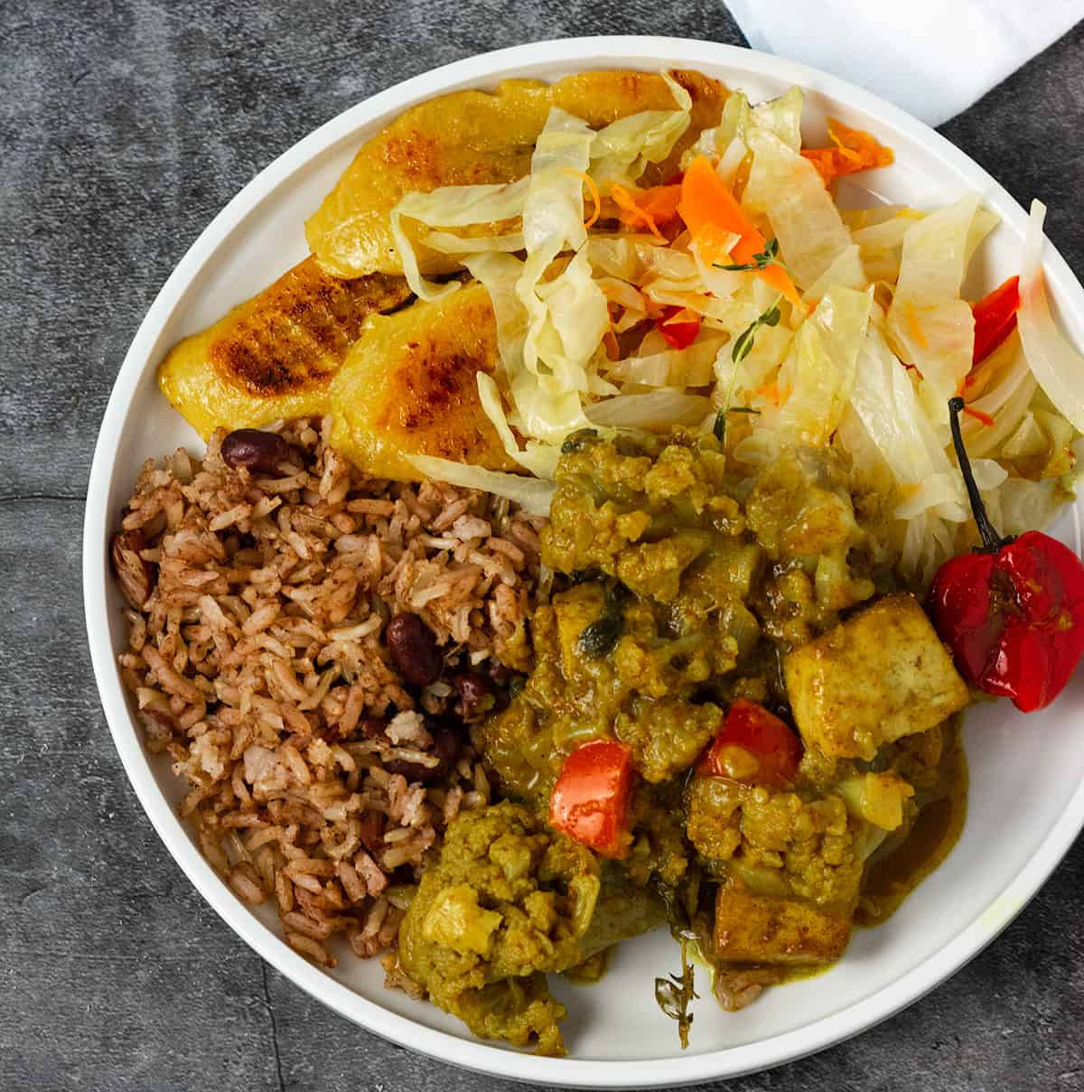 curry, rice, cabbage, and plantains on a white plate