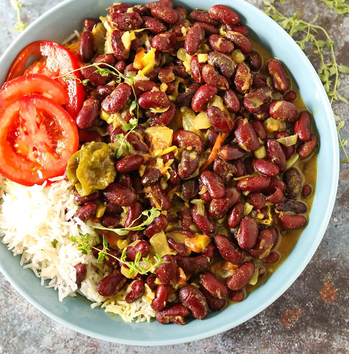 close up kidney bean curry Jamaican style with white rice tomato slices in a blue bowl with a fork on a blue and brown concrete background garnished with thyme