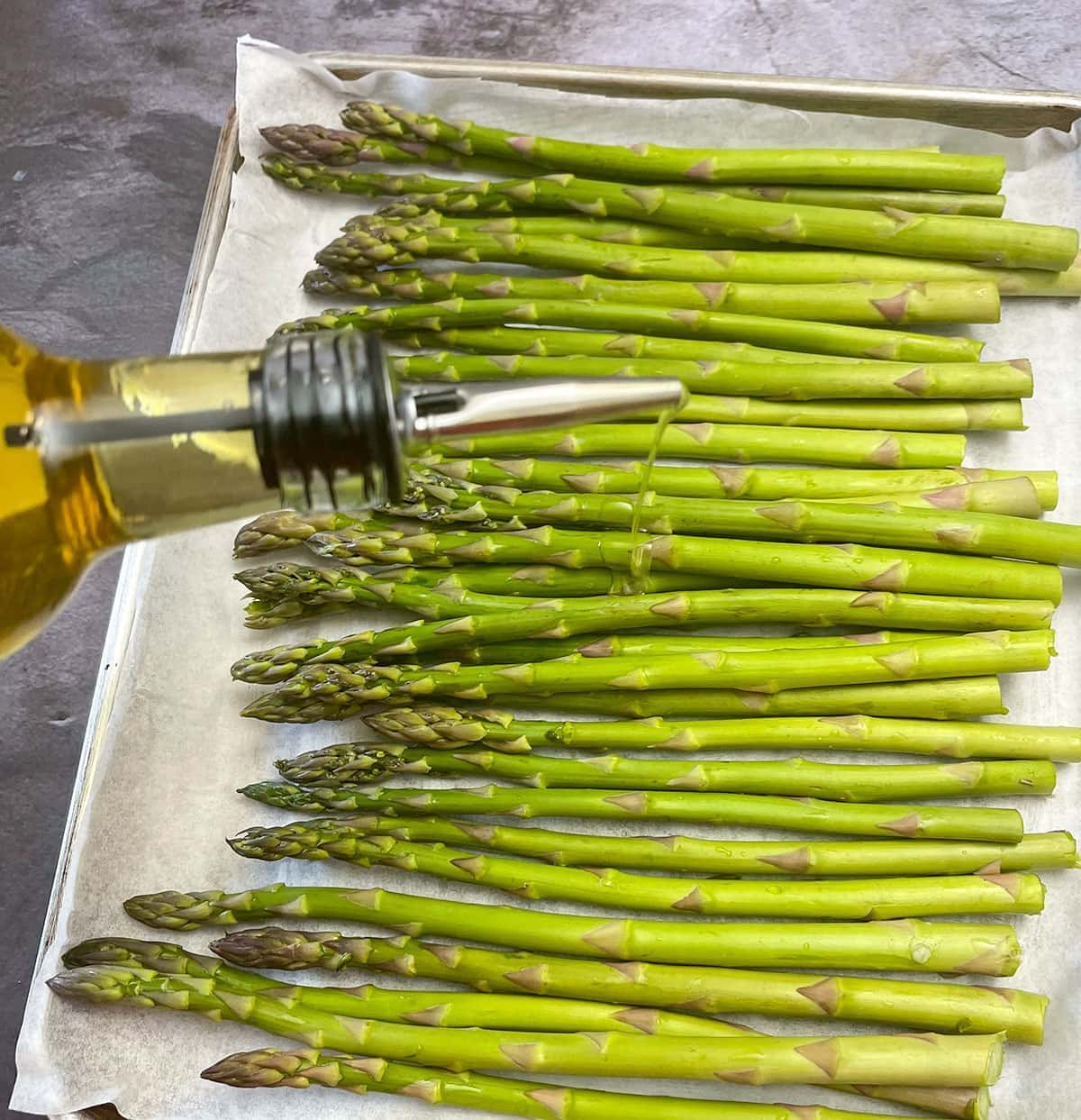 asparagus with olive oil on a baking sheet