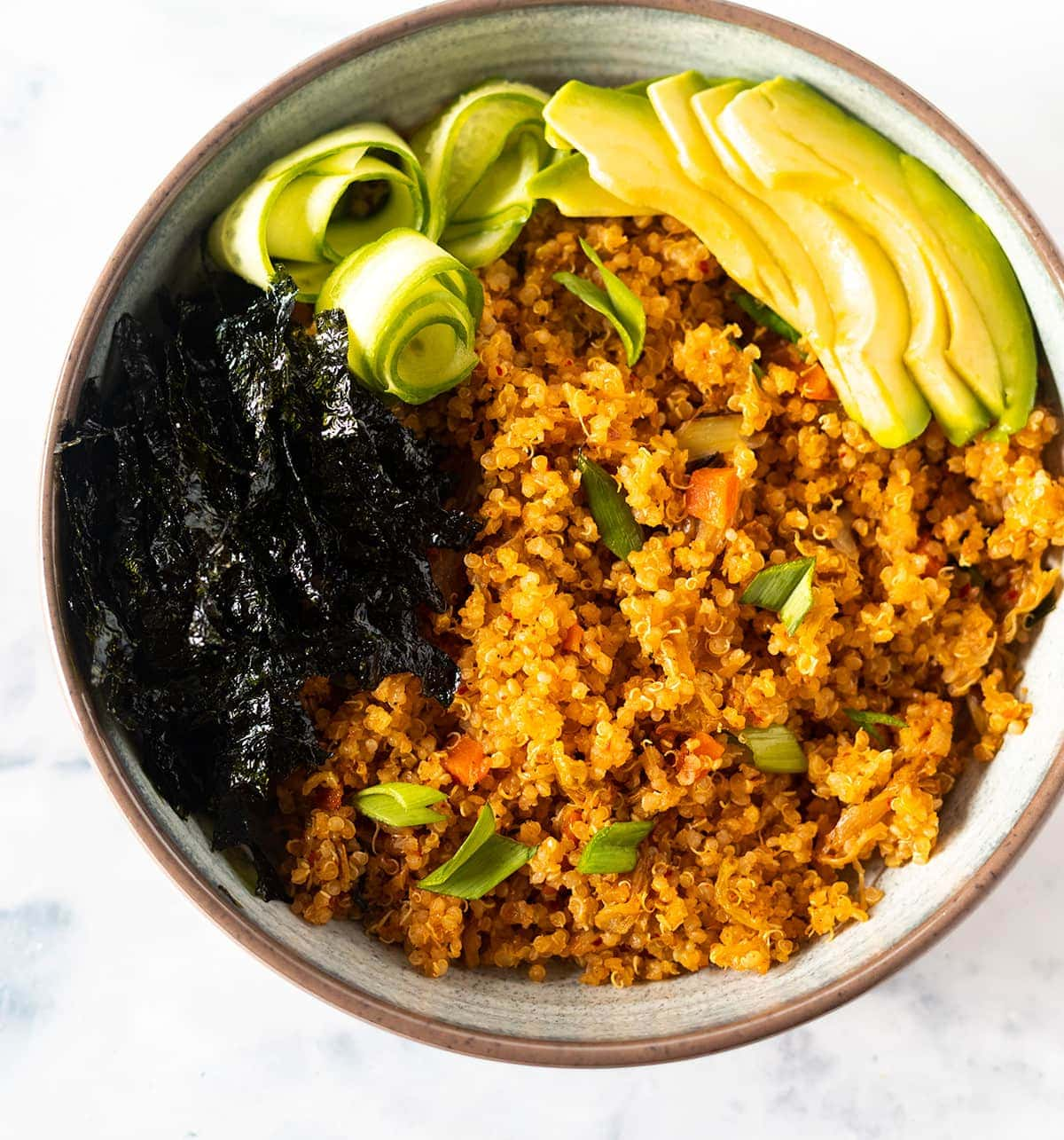 Close up kimchi fried quinoa in a beige bowl with avocado slices, nori strips and cucumber roses